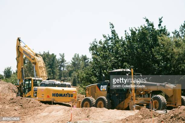 Komatsu and Caterpillar construction vehicles are visible among piles of dirt at the Apple Park known colloquially as 'The Spaceship' the new...
