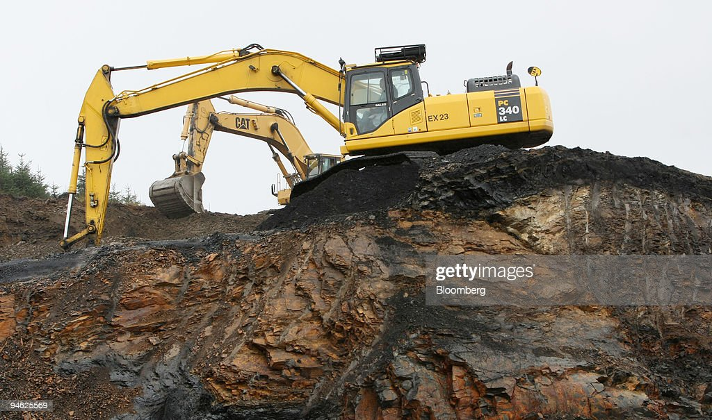 Komatsu foreground and Caterpillar mechanical diggers harvest anthracite coal at the opencast mining pits at Aberpergwm Colliery outside Glynneath...