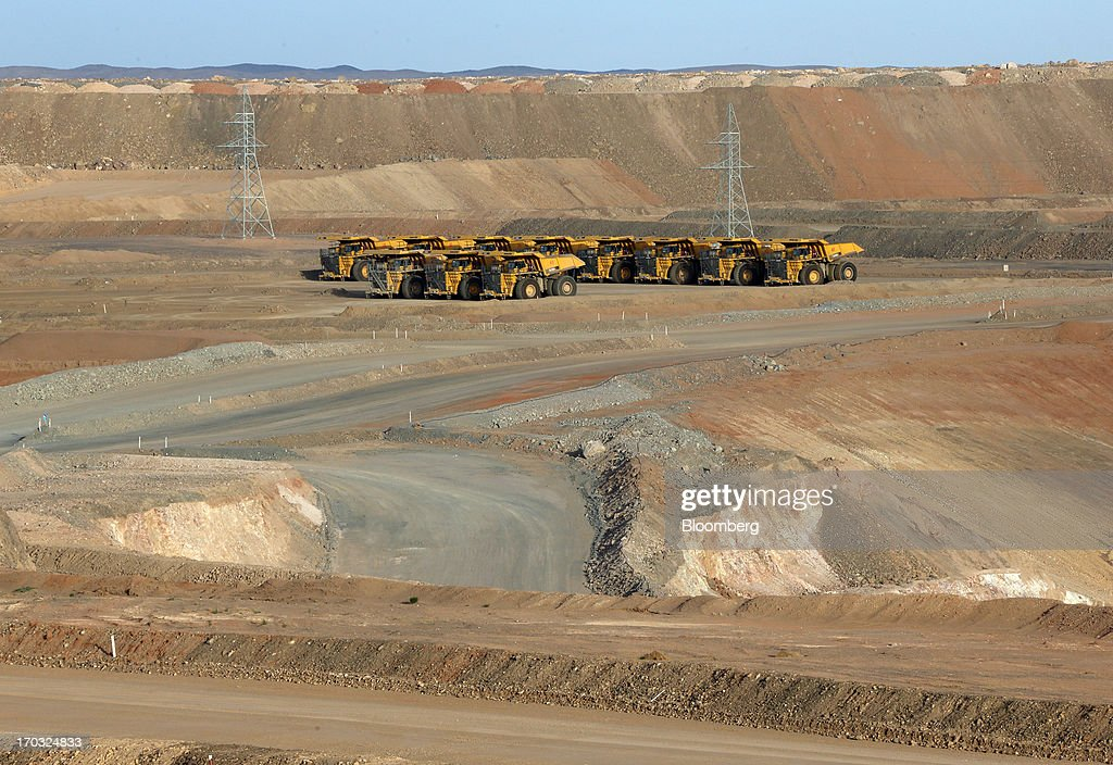 Komatsu Ltd. dump trucks sit at the open pit of the Oyu Tolgoi copper-gold mine, jointly owned by Rio Tinto Group's unit Turquoise Hill Resources Ltd. and Erdenes Oyu Tolgoi LLC, in Khanbogd, the South Gobi desert, Mongolia, on Thursday, June 6, 2013. Rio Tinto, the world's second-biggest mining company, is expected to start first shipments from its $6.6 billion copper-gold mine in Mongolia this month. Photographer: Tomohiro Ohsumi/Bloomberg via Getty Images