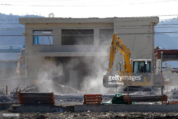 A Komatsu Ltd excavator operates in an area damaged by the tsunami following the Great East Japan Earthquake and Tsunami in Minamisanriku Miyagi...