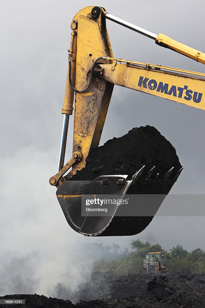 A Komatsu Ltd. excavator operates in the smoke at the PT Exploitasi Energi Indonesia open pit coal mine in Palaran, East Kalimantan province, Indonesia, on Friday, Sept. 13, 2013. Prices of power-station coal in Indonesia, the worlds biggest exporter, may be little changed in coming weeks, according to Bloomberg News survey. Photographer: Dadang Tri/Bloomberg via Getty Images