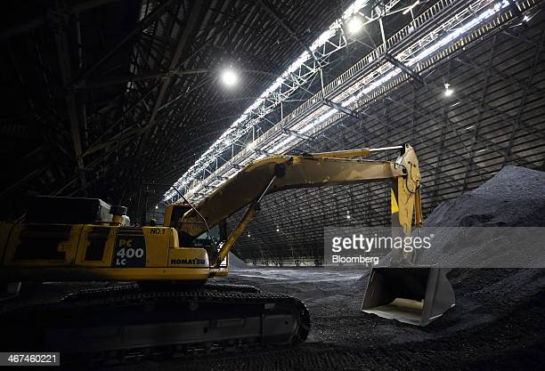 A Komatsu Ltd excavator stands inside a coal storage yard at the Joban Joint Power Co Nakoso coalfired power station in Iwaki City Fukushima...
