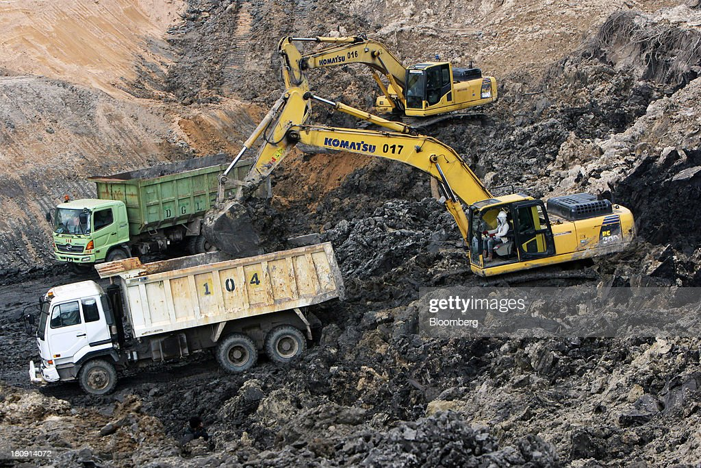 Komatsu Ltd. excavators load trucks at the PT Exploitasi Energi Indonesia open pit coal mine in Palaran, East Kalimantan province, Indonesia, on Friday, Sept. 13, 2013. Prices of power-station coal in Indonesia, the worlds biggest exporter, may be little changed in coming weeks, according to Bloomberg News survey. Photographer: Dadang Tri/Bloomberg via Getty Images