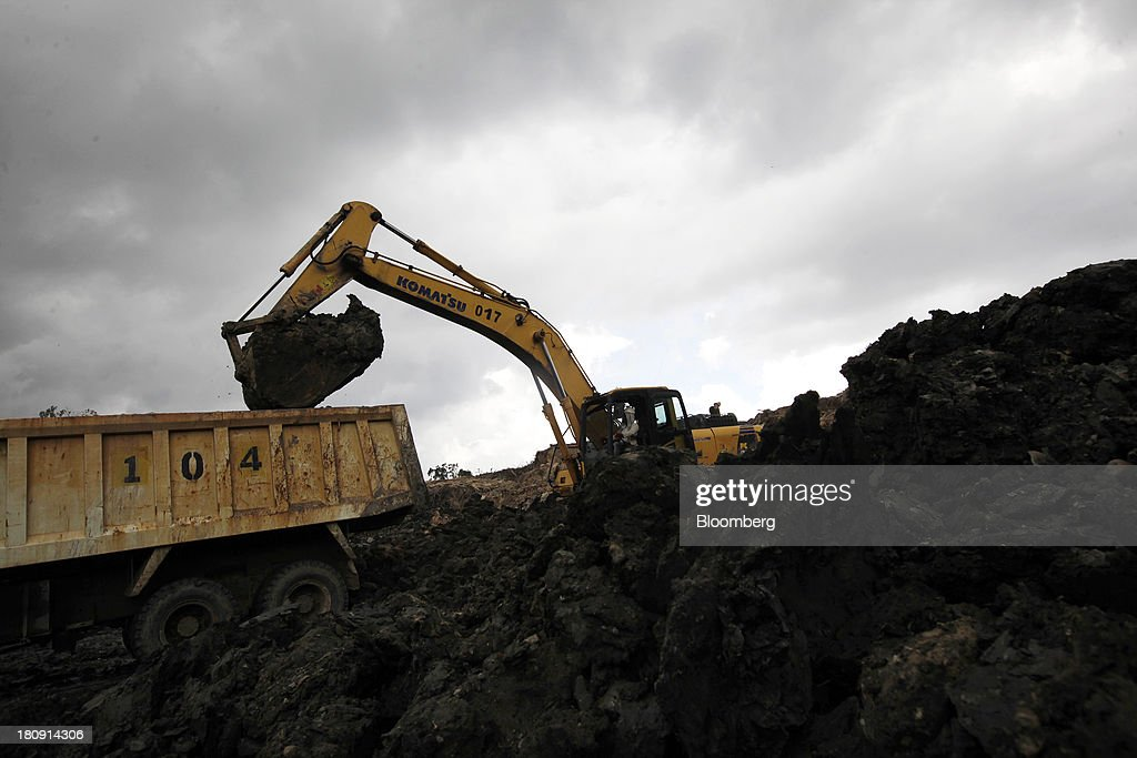 A Komatsu Ltd. excavators loads a truck at the PT Exploitasi Energi Indonesia open pit coal mine in Palaran, East Kalimantan province, Indonesia, on Friday, Sept. 13, 2013. Prices of power-station coal in Indonesia, the worlds biggest exporter, may be little changed in coming weeks, according to Bloomberg News survey. Photographer: Dadang Tri/Bloomberg via Getty Images