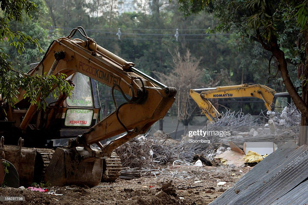 Komatsu Ltd. excavators stand on a demolition site in a side street off Langsuan road in Bangkok, Thailand, on Tuesday, Dec. 11, 2012. The Crown Property Bureau owns about 41,300 rai (66 square kilometers) of land across the country, about a fifth of which is in Bangkok, according to Aviruth Wongbuddhapitak, an adviser to the CPB who sits on the board of two of its subsidiaries. Photographer: Dario Pignatelli/Bloomberg via Getty Images