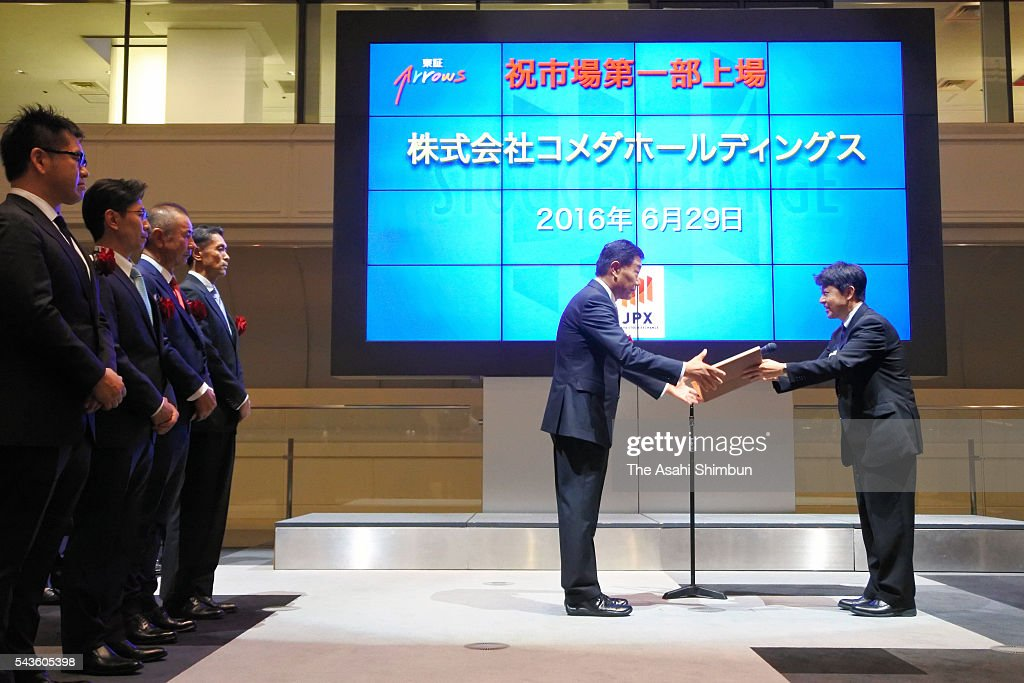 Komeda Holdings president Okitane Usui (C) receives the document during the ceremony to mark the company is listed on the first section at the Tokyo Stock Exchange on June 29, 2016 in Tokyo, Japan.
