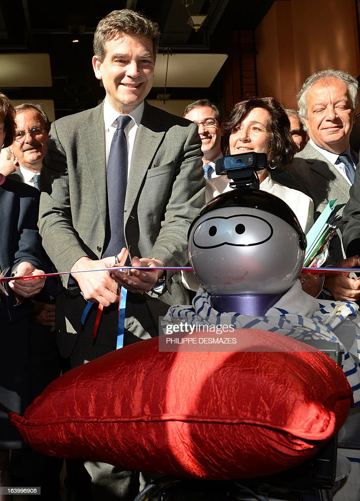 A Kompai robot carries a red pillow as France's Industrial Renewal minister Arnaud Montebourg cuts a tricolor ribbon on March 19, 2013 during the inaugural ceremony of the Innorobo 2013 European summit in Lyon, southeastern France.