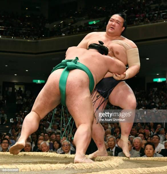 Komusubi Yoshikaze pushes Yokozuna Kisenosato out of the ring to win during day one of the Grand Sumo Summer Tournament at Ryogoku Kokugikan on May...