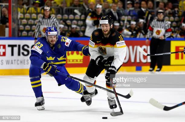 Konrad Abeltshauser of Germany challenges Oliver Ekman Larsson of Sweden for the puck during the 2017 IIHF Ice Hockey World Championship game between...