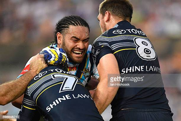 Konrad Hurrell of the Titans is tackled by Johnathan Thurston and Scott Bolton of the Cowboys during the round 26 NRL match between the North...