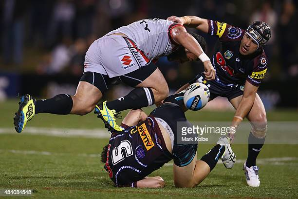 Konrad Hurrell of the Warriors is tackled by Joshua Mansour and Jamie Soward of the Panthers during the round 23 NRL match between the Penrith...