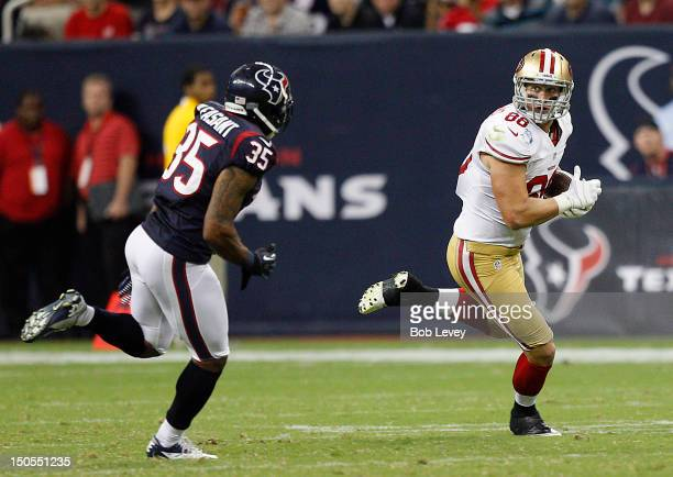 Konrad Reuland of the San Francisco 49ers runs in the flat after making a reception as Eddie Pleasant of the Houston Texans pursues during preseason...