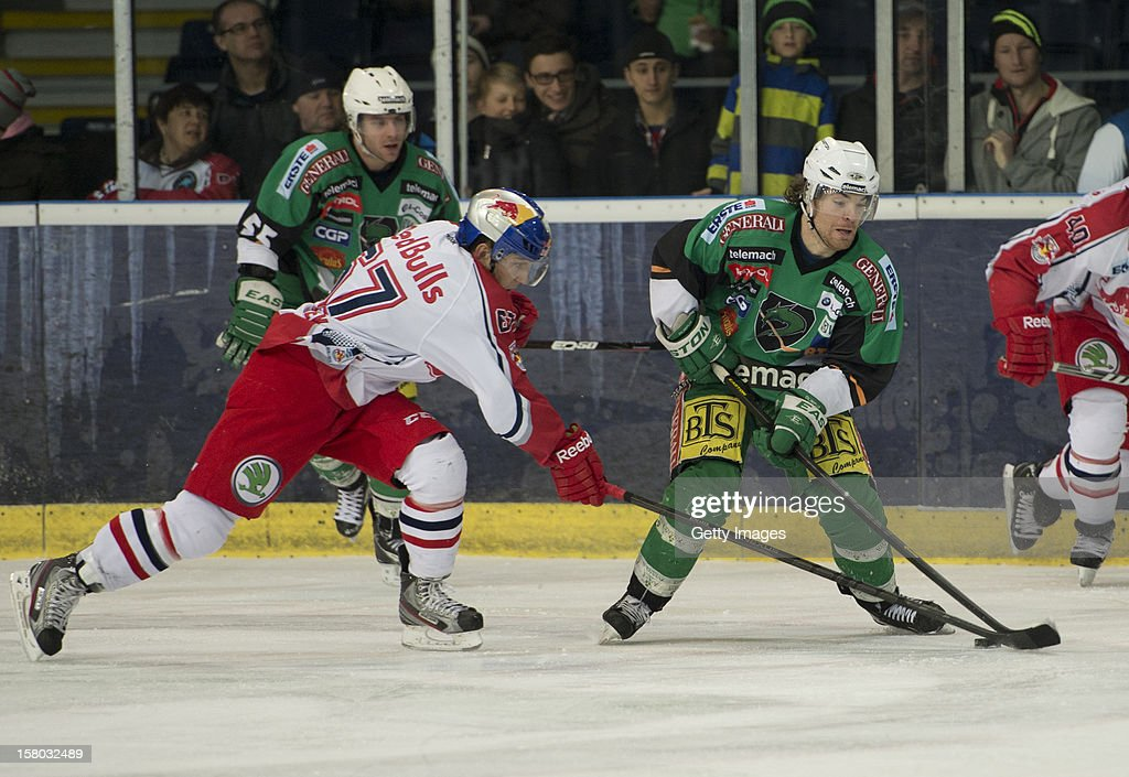 Konstantin Komarek of Salzburg (left) challenges Brock Mcbride of Ljubljana during the Erste Bank Eishockey Liga match between EC Red Bull Salzburg and HDD TELEMACH Olimpija Ljubljana at Eisarena Salzburg on December 9, 2012 in Salzburg, Austria.