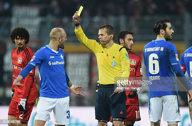 Konstantin Rausch of Darmstadt is shown an yellow card by referee Dr Jochen Drees during the match between SV Darmstadt 98 and Bayer Leverkusen at...