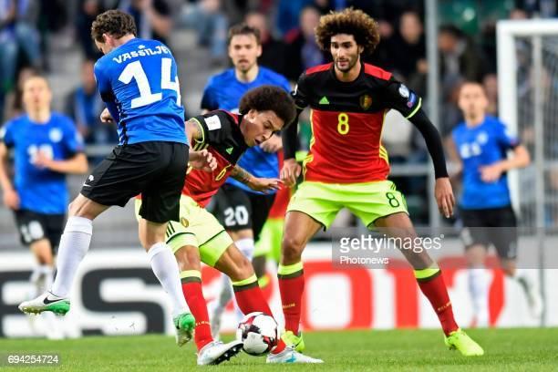Konstantin Vassiljev midfielder of Estonia battles for the ball with Axel Witsel midfielder of Belgium and Marouane Fellaini midfielder of Belgium...