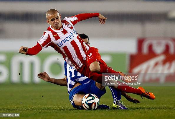 Konstantinos Giannoulis of Atromitos slides into Vladimir Weiss of Olympiacos during the Superleague match between Atromitos FC and Olympiacos at...