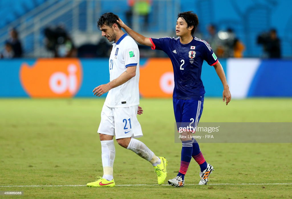 Konstantinos Katsouranis of Greece is consoled by Atsuto Uchida of Japan while walking off the pitch after receiving a red card during the 2014 FIFA World Cup Brazil Group C match between Japan and Greece at Estadio das Dunas on June 19, 2014 in Natal, Brazil.