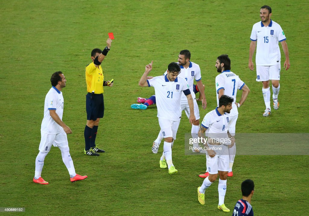 Konstantinos Katsouranis #21 of Greece is shown a red card after receiving his second yellow by referee Joel Aguilar during the 2014 FIFA World Cup Brazil Group C match between Japan and Greece at Estadio das Dunas on June 19, 2014 in Natal, Brazil.