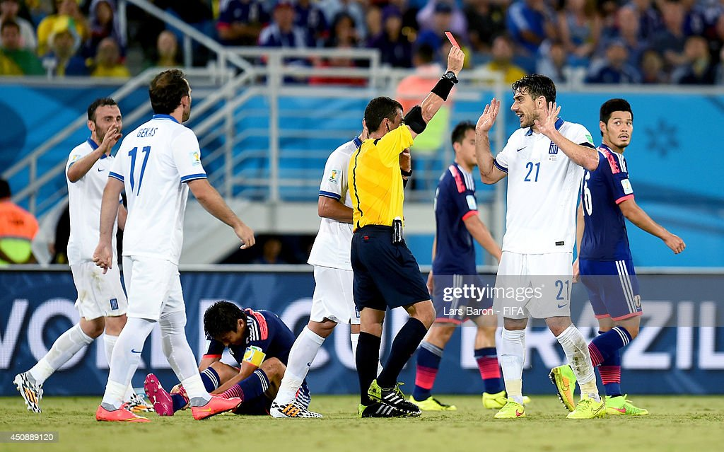 Konstantinos Katsouranis of Greece receives a red card by referee Joel Aguilar during the 2014 FIFA World Cup Brazil Group C match between Japan and Greece at Estadio das Dunas on June 19, 2014 in Natal, Brazil.