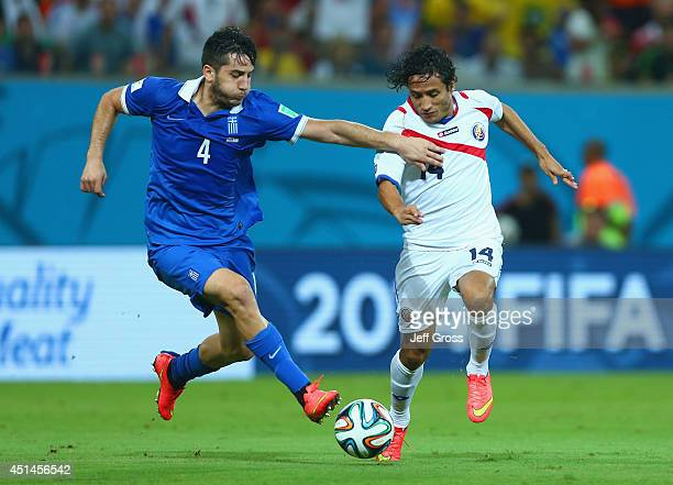 Konstantinos Manolas of Greece is challenged by Randall Brenes of Costa Rica during the 2014 FIFA World Cup Brazil Round of 16 match between Costa...