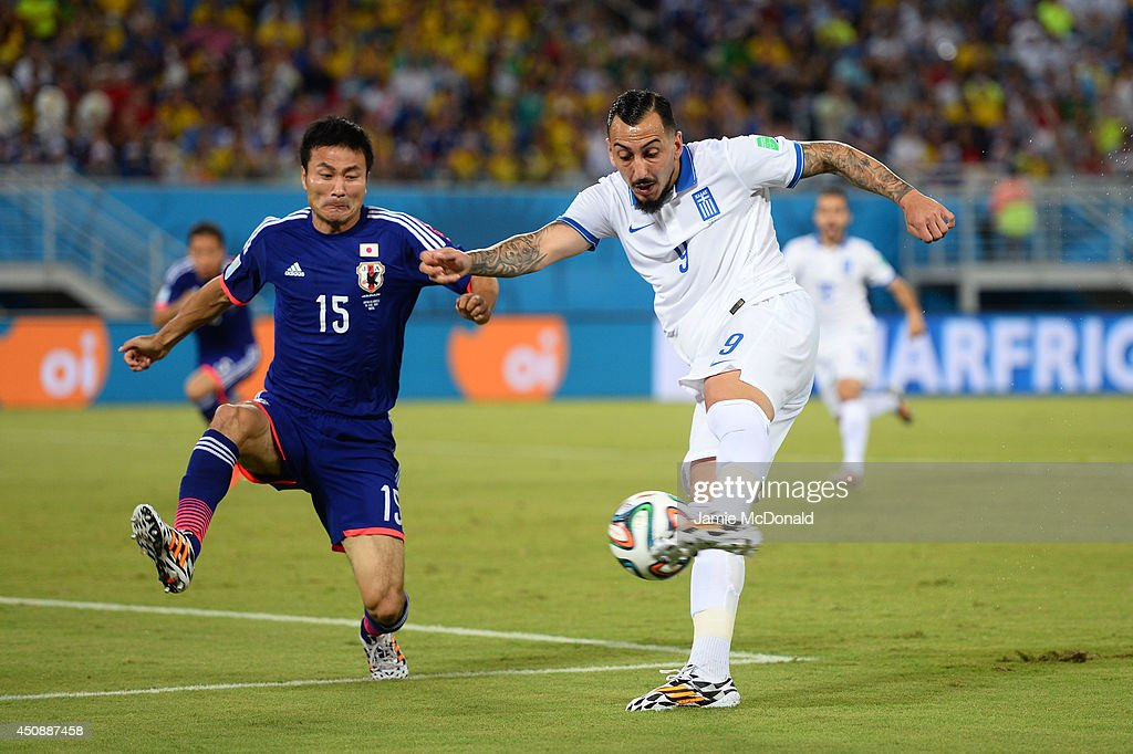 Konstantinos Mitroglou of Greece strikes the ball against <a gi-track='captionPersonalityLinkClicked' href=/galleries/search?phrase=Yasuyuki+Konno&family=editorial&specificpeople=2358762 ng-click='$event.stopPropagation()'>Yasuyuki Konno</a> of Japan during the 2014 FIFA World Cup Brazil Group C match between Japan and Greece at Estadio das Dunas on June 19, 2014 in Natal, Brazil.