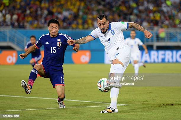 Konstantinos Mitroglou of Greece strikes the ball against Yasuyuki Konno of Japan during the 2014 FIFA World Cup Brazil Group C match between Japan...