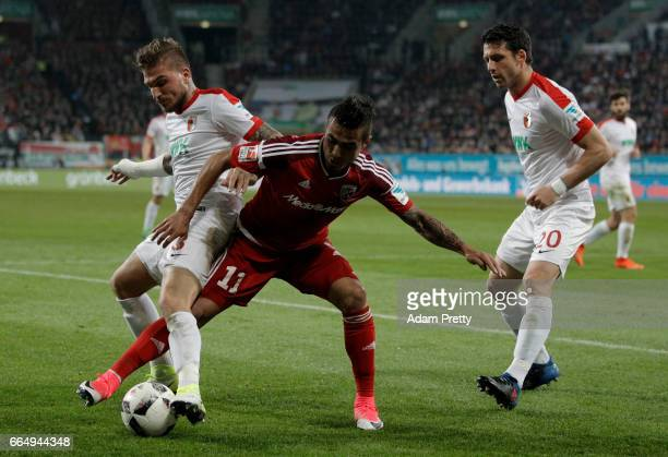 Konstantinos Stafylidis of Augsburg and Dario Lezcano Farina of Ingolstadt battle for the ball during the Bundesliga match between FC Augsburg and FC...