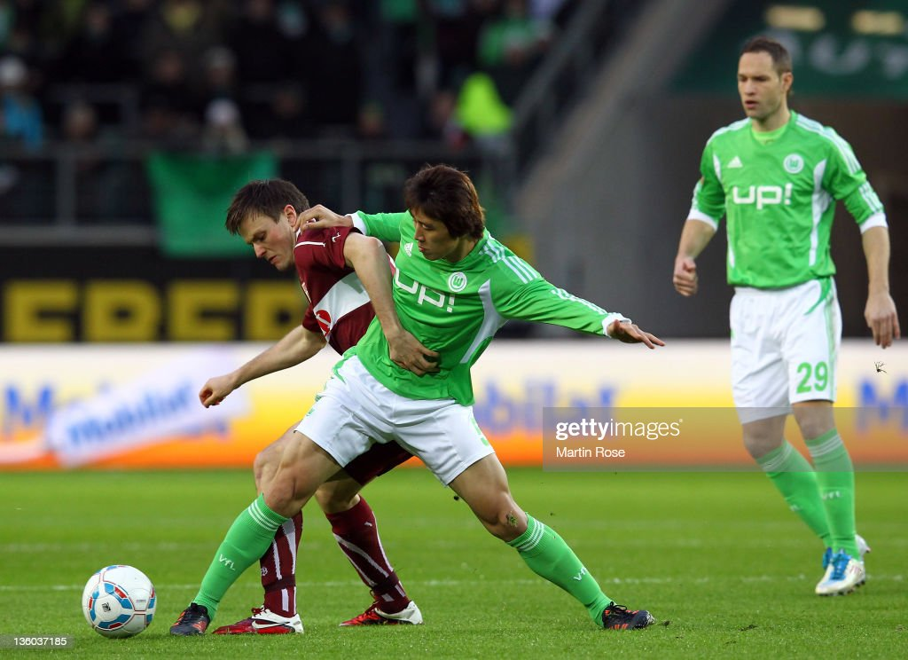 Koo Ja Cheol of Wolfsburg and William Kvist of Stuttgart battle for the ball during the Bundesliga match between VfL Wolfsburg and VfB Stuttgart at...