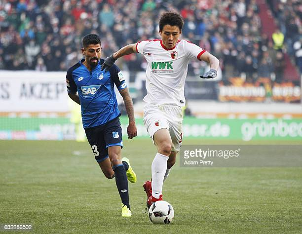 Koo JaCheol of Augsburg is challenged by Kerem Demirbay of 1899 Hoffenheim during the Bundesliga match between FC Augsburg and TSG 1899 Hoffenheim at...