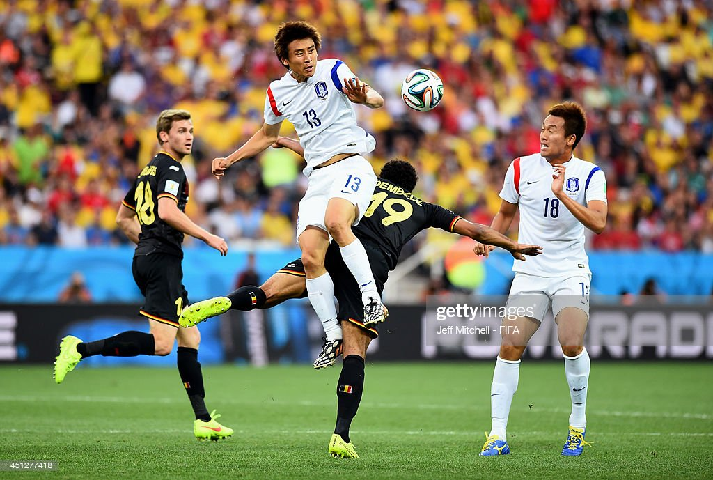 Koo JaCheol of South Korea and Moussa Dembele of Belgium compete for the ball during the 2014 FIFA World Cup Brazil Group H match between Korea...