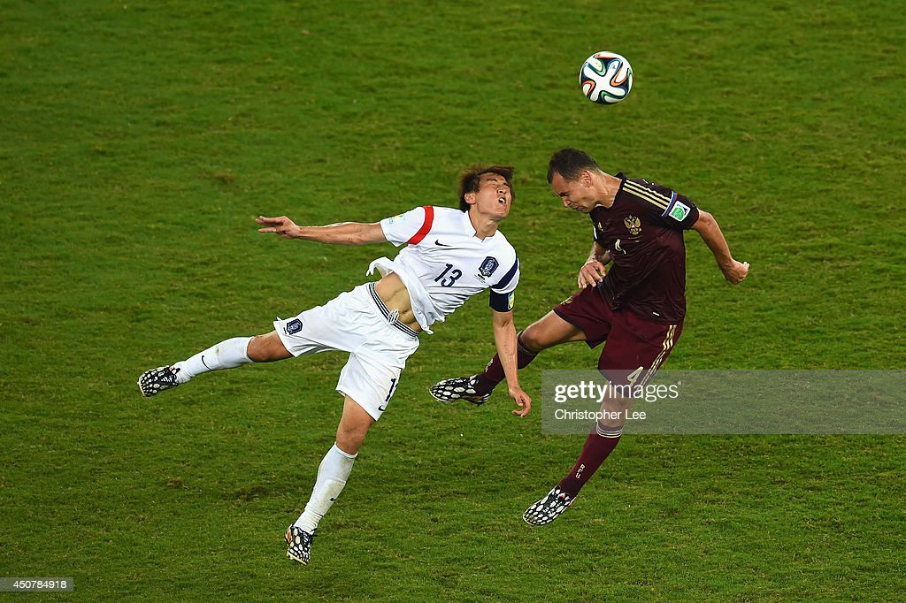 Koo JaCheol of South Korea and Sergey Ignashevich of Russia go up for a header during the 2014 FIFA World Cup Brazil Group H match between Russia and...