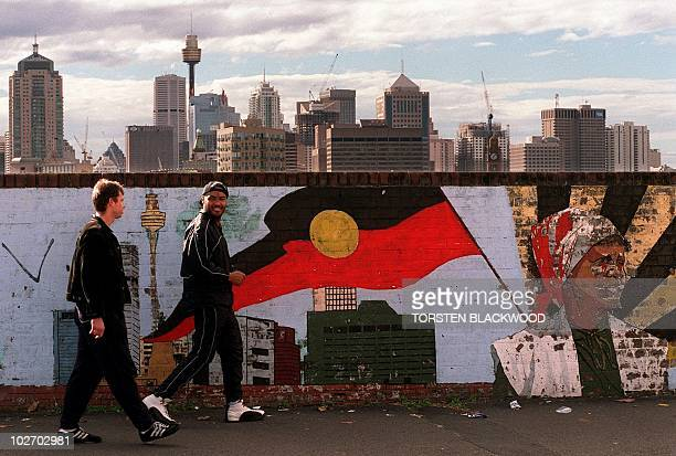 A Koori youth walks with his white friend past a mural depicting the Aboriginal flag flying over the modern Sydney skyline 06 July The upper house...