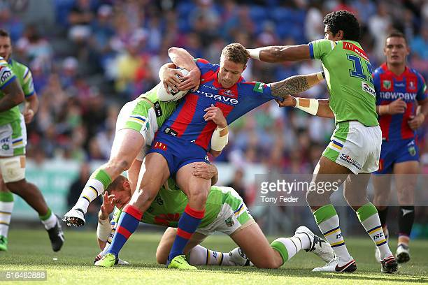 Korbin Sims of the Knights is tackled by the Raiders defence during the round three NRL match between the Newcastle Knights and the Canberra Raiders...