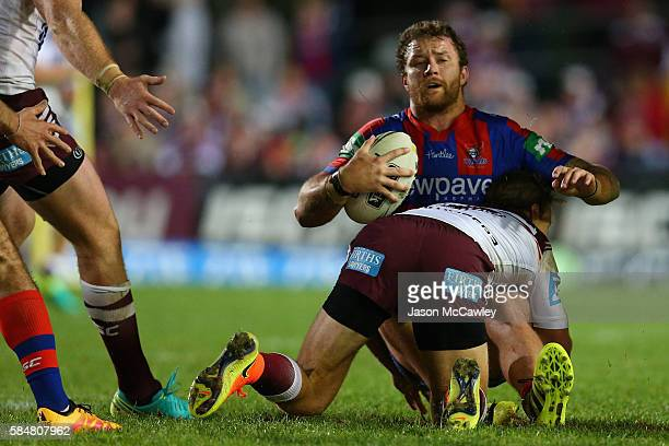 Korbin Sims of the Knights is tackled during the round 21 NRL match between the Manly Sea Eagles and the Newcastle Knights at Brookvale Oval on July...