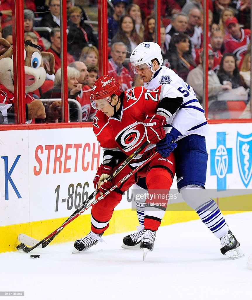 Korbinian Holzer #55 of the Toronto Maple Leafs battles for a puck along the boards with Alexander Semin #28 of the Carolina Hurricanes during play at PNC Arena on February 14, 2013 in Raleigh, North Carolina.