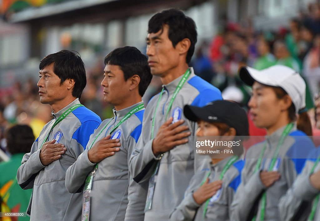 Korea Republic coach Jong Songchon (L) and his backroom staff line up for the National Anthem ahead of the FIFA U-20 Women's World Cup Canada 2014 Group D match between Korea Republic and Mexico at the National Soccer Stadium on August 13, 2014 in Toronto, Canada.