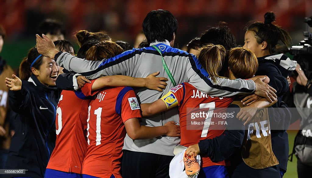 Korea Republic coach Jong Songchon gets a hug from his players after victory in the FIFA U-20 Women's World Cup Canada 2014 Group D match between Korea Republic and Mexico at the National Soccer Stadium on August 13, 2014 in Toronto, Canada.