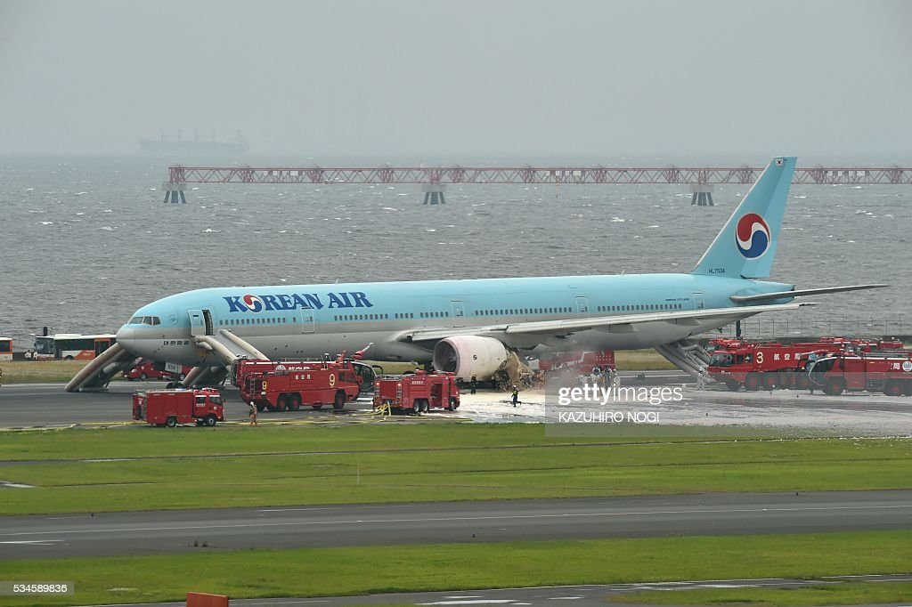 A Korean Air Boeing 777 is seen on a runway in Tokyo's Haneda Airport on May 27, 2016. About 300 passengers and crew members were evacuated from the plane after one of the engines caught fire, official said on May 27. / AFP / KAZUHIRO
