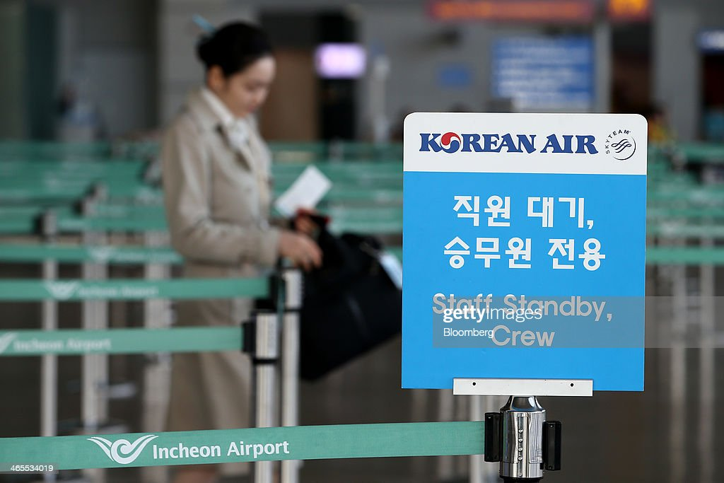 A Korean Air Lines Co. flight attendant walks past signage for the staff check-in counter at Incheon International Airport in Incheon, South Korea, on Monday, Jan. 27, 2014. Korean Air, the nation's biggest carrier, is scheduled to report full-year results on Feb. 3. Photographer: SeongJoon Cho/Bloomberg via Getty Images