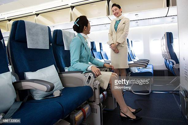 Korean Air Lines Co flight attendants chat inside the companys Boeing Co 7478 passenger aircraft during a media preview at Incheon International...