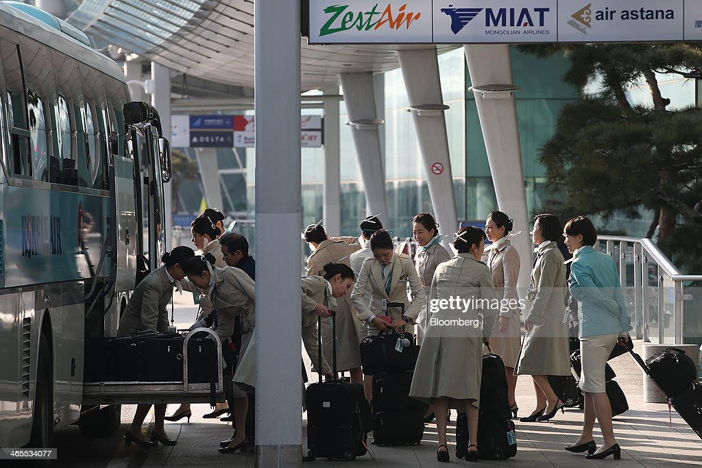 Korean Air Lines Co. flight attendants load their luggage onto a bus at Incheon International Airport in Incheon, South Korea, on Monday, Jan. 27, 2014. Korean Air, the nation's biggest carrier, is scheduled to report full-year results on Feb. 3. Photographer: SeongJoon Cho/Bloomberg via Getty Images