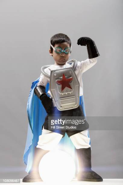 Korean boy in superhero costume standing over glowing orb
