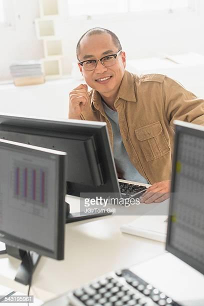 Korean businessman smiling at computer at office desk