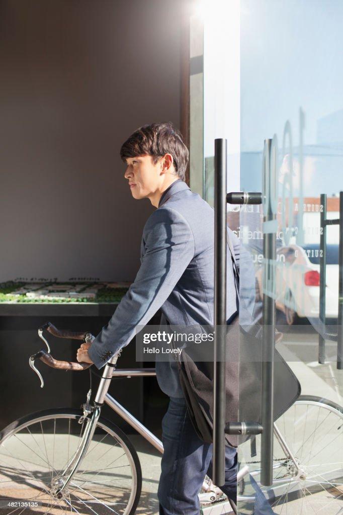 Korean businessman wheeling bicycle in office