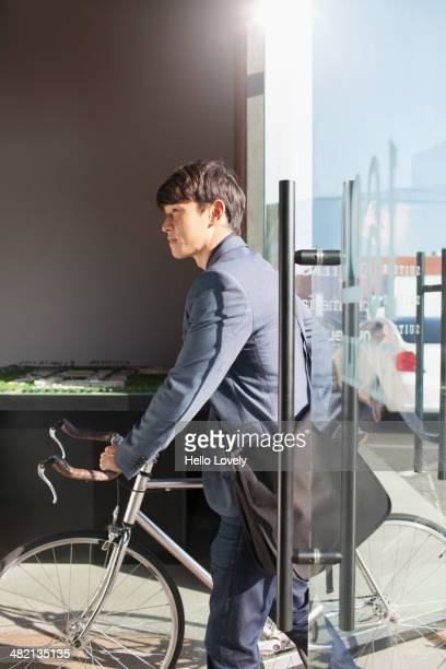 Korean businessman wheeling bicycle in office