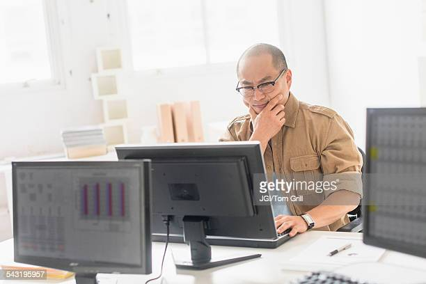 Korean businessman working on computer at office desk
