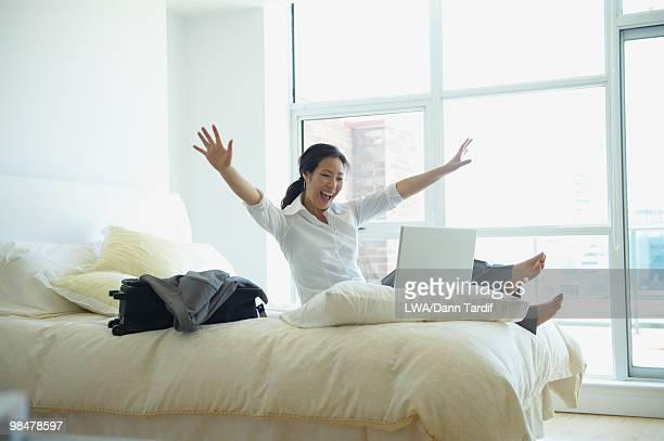 Korean businesswoman working and cheering in hotel room