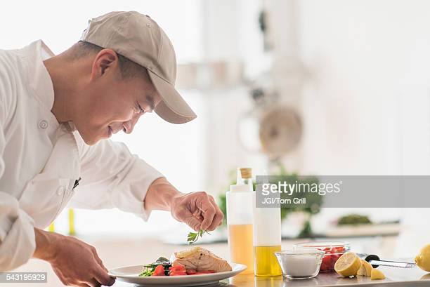 Korean chef preparing meal in kitchen