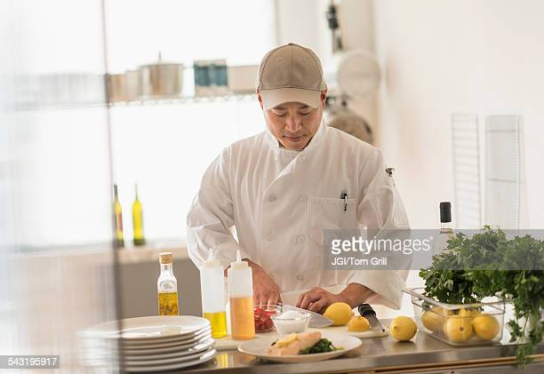 Korean chef slicing food in kitchen