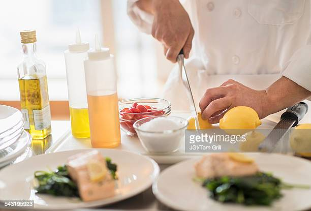 Korean chef slicing lemons in kitchen